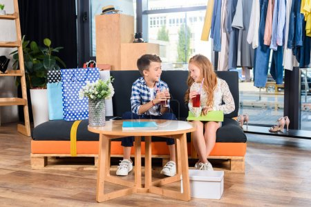 Photo for Happy brother and sister with beverages sitting on sofa in boutique during shopping - Royalty Free Image