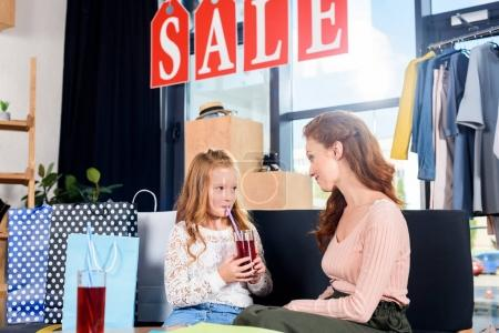 mother and daughter in boutique during sale