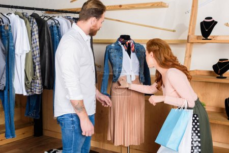 Photo for Couple choosing clothes on shopping in boutique - Royalty Free Image