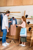 couple choosing clothes in n boutique