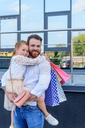 Photo pour Père tient le bras de sa fille souriante avec des sacs à provisions - image libre de droit