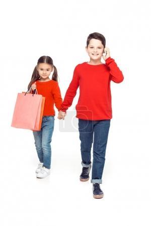 Photo pour Frères et sœurs de chandails rouges avec des sacs à provisions, isolés sur blanc - image libre de droit