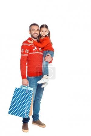 Photo pour Père et fille de chandails rouges portant les sacs shopping, isolés sur blanc - image libre de droit