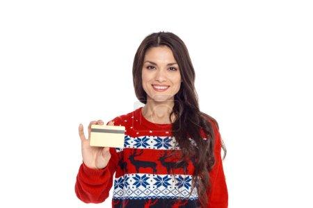 Photo pour Femme souriante en pull de Noël rouge tenant la carte de crédit, isolé sur blanc - image libre de droit