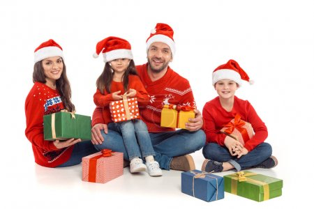 Photo for Happy family in santa hats with christmas presents, isolated on white - Royalty Free Image
