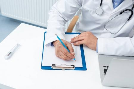 Doctor writing in clipboard