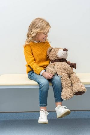 girl doing neurology examination of teddy bear