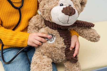 Photo for Cropped shot of girl with stethoscope listening to teddy bear breath - Royalty Free Image