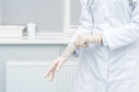 Photo for Cropped shot of female doctor putting on medical gloves - Royalty Free Image