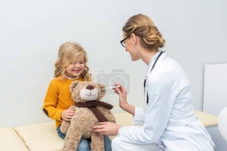 Doctor measuring temperature of teddy bear