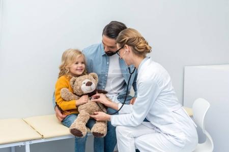 doctor listening to breath of teddy bear