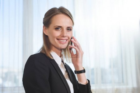 Photo for Beautiful young businesswoman talking on smartphone and smiling at camera - Royalty Free Image