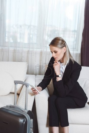 businesswoman with smartphone in hotel room