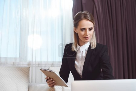businesswoman taking notes in hotel room