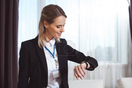 Photo pour Belle jeune femme d'affaires souriante vérifier montre-bracelet - image libre de droit
