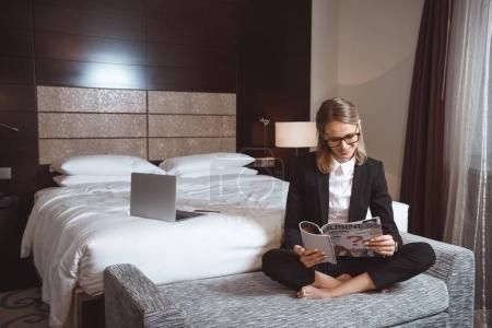Photo for Smiling young businesswoman in eyeglasses reading magazine while sitting in hotel room - Royalty Free Image