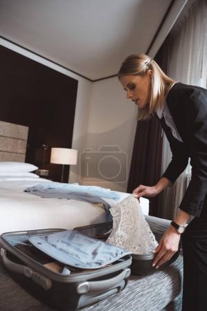 Photo pour Séduisante jeune femme d'affaires déballage valise dans la chambre d'hôtel - image libre de droit