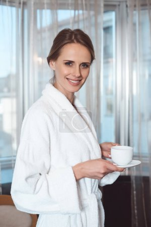 Woman in bathrobe drinking coffee