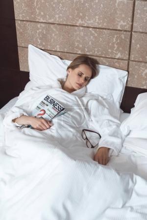 Photo pour Jeune femme tenant magazine tout en dormant sur le lit dans la chambre d'hôtel - image libre de droit