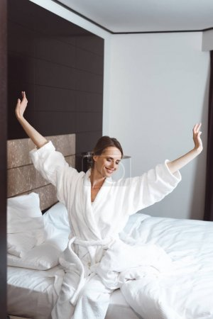 Photo for Smiling young woman in bathrobe stretching while waking up in hotel room - Royalty Free Image