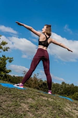 Photo for Attractive young athletic woman stretching before training outdoors - Royalty Free Image