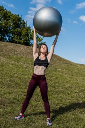 woman holding fitball over head