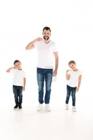 Photo pour Jeune père et les enfants regardant caméra tout en brossant les dents ensemble isolé sur blanc - image libre de droit