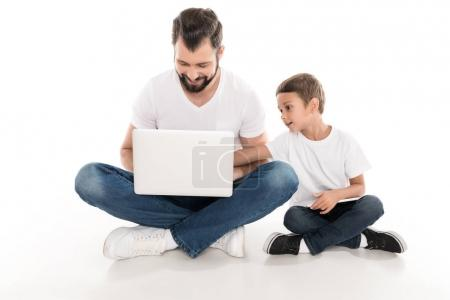 Photo for Smiling father and little son using laptop together isolated on white - Royalty Free Image