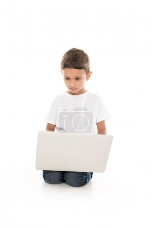 Photo for Focused little boy using laptop isolated on white - Royalty Free Image