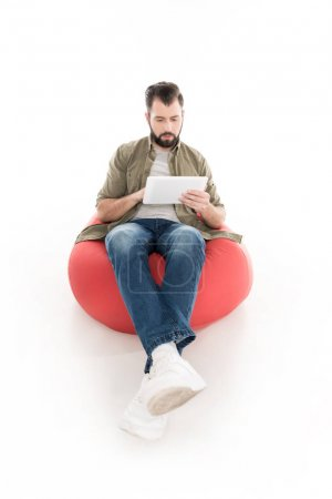 Photo for Man using digital tablet while sitting on bean bag chair, isolated on white - Royalty Free Image