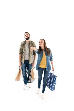 Photo pour Couple pendant les achats avec des sacs en papier, isolé sur blanc - image libre de droit