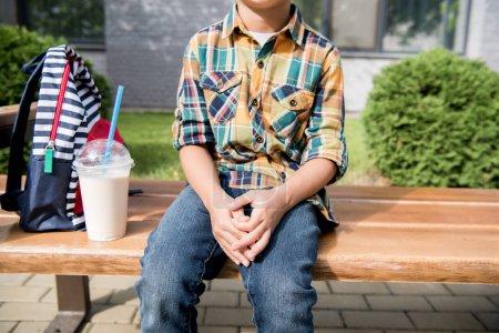 Boy with backpack and milkshake