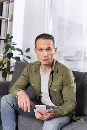 Photo for Portrait of man with smartphone looking at camera at home - Royalty Free Image