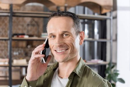 Photo pour Portrait d'un homme souriant parlant sur smartphone à la maison - image libre de droit