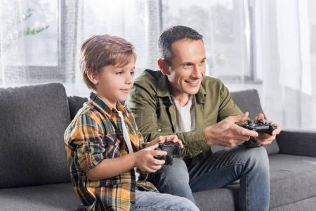 father and son playing console with gamepads