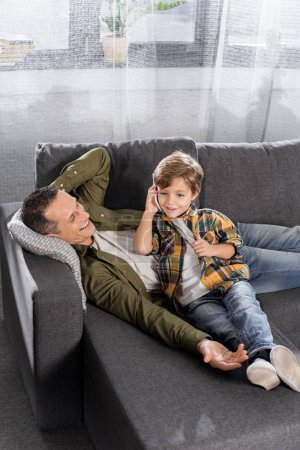 kid talking by phone while father resting