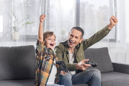 Photo for Portrait of excited father and son playing video game together at home - Royalty Free Image