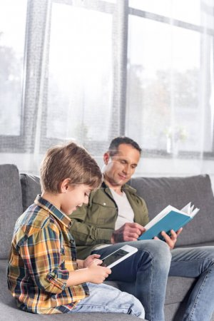father with book and son with tablet