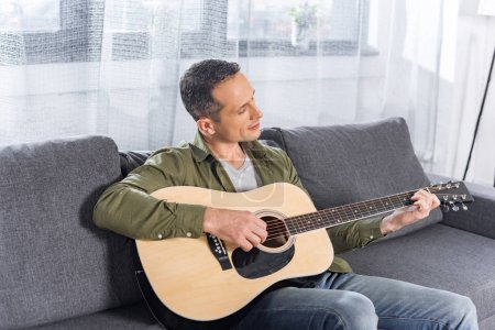 Photo for Portrait of smiling man playing guitar at home - Royalty Free Image