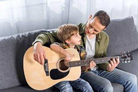 Photo for Handsome happy father and little son playing guitar together - Royalty Free Image
