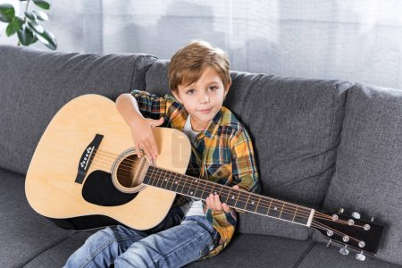 Photo for Little boy with acoustic guitar in hand resting on sofa at home - Royalty Free Image