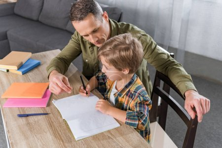 Photo for Father and little son doing homework together at home - Royalty Free Image
