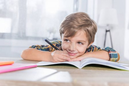 Photo for Happy little schoolboy doing homework and writing in notebook - Royalty Free Image