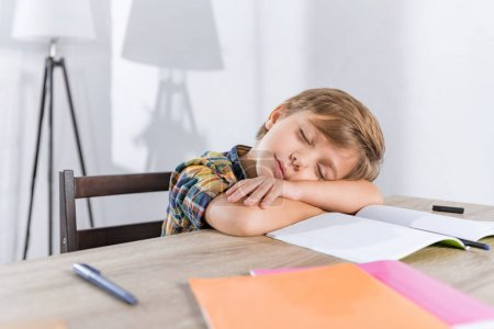 little boy sleeping on table