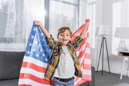 Photo pour Portrait de heureux petit garçon avec drapeau américain dans les mains regardant la caméra à la maison - image libre de droit