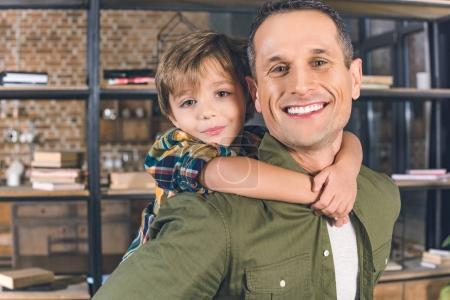 Photo for Portrait of little son hugging smiling father at home - Royalty Free Image