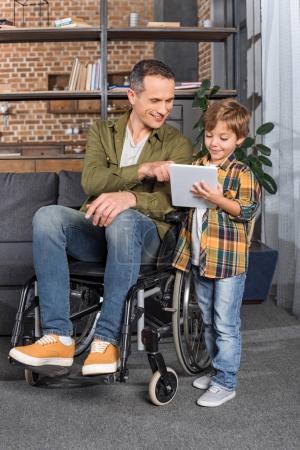 Photo pour Homme souriant en fauteuil roulant et petit fils en utilisant la tablette ensemble à la maison - image libre de droit