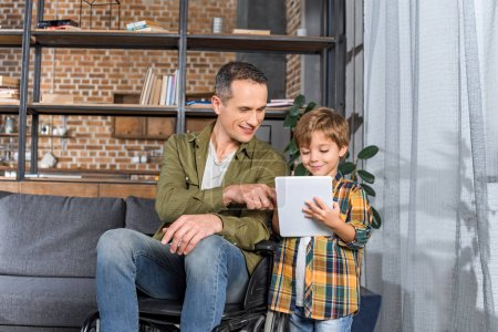 father in wheelchair and son using tablet