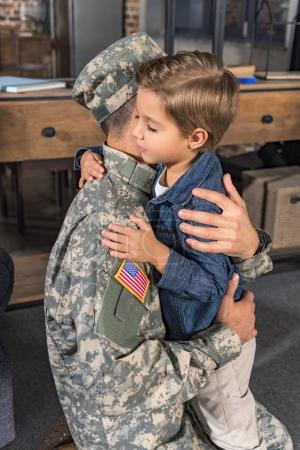 father in military uniform hugging son