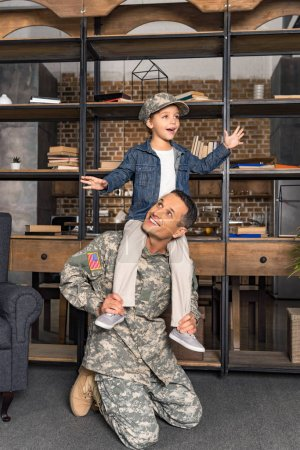 son riding on military father shoulders